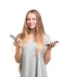 Una muchacha linda en una camiseta gris larga con el pelo rubio ligero encantador está sosteniendo dos smartphones aislados en un Fotos de archivo libres de regalías