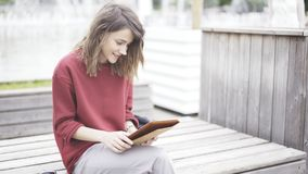 Una muchacha linda joven que se sienta en el parque con una tableta Imágenes de archivo libres de regalías