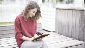 Una muchacha linda joven que se sienta en el parque con una tableta Foto de archivo