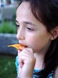 Una muchacha linda que come microprocesadores fotografía de archivo