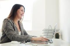 Una muchacha más joven que trabaja en la oficina en la tabla fotografía de archivo