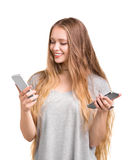 Una muchacha magnífica en una camiseta gris larga con el pelo rubio ligero está sosteniendo dos smartphones, aislados en un fondo Imagen de archivo libre de regalías