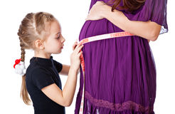 Una muchacha mide el vientre de su madre Imagen de archivo libre de regalías