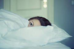 Una muchacha miente en cama puede el ` t caerse pensamiento y sueño dormidos insomnio psicología Imagen de archivo libre de regalías