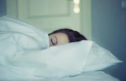 Una muchacha miente en cama puede el ` t caerse pensamiento y sueño dormidos insomnio psicología Imagenes de archivo