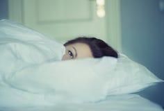 Una muchacha miente en cama puede el ` t caerse pensamiento y sueño dormidos insomnio psicología Fotos de archivo