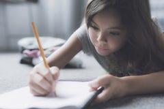 Una muchacha miente en el piso gris al lado de la cama y dibuja algo en su cuaderno blanco para dibujar con un lápiz Foto de archivo