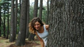 Una muchacha mira hacia fuera de detrás un árbol y tienta un finger a ella almacen de video