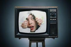 Una muchacha mira hacia fuera de la TV. Imagen de archivo