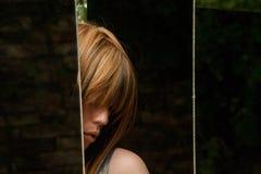 Una muchacha mira hacia fuera entre los espejos Fotos de archivo