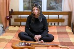 Una muchacha mira la guitarra eléctrica que se sienta en la cama Fotos de archivo libres de regalías