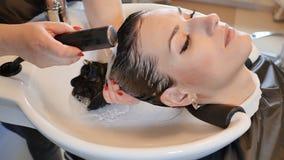 Una muchacha morena con el pelo largo visita un salón de belleza Lavado del pelo almacen de video