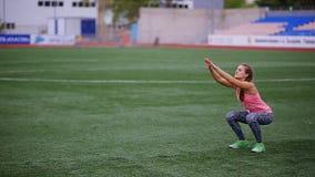 Una muchacha muscular hermosa en medias y un chaleco hace un calentamiento en el estadio Crossfit, aptitud, forma de vida sana metrajes