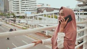 Una muchacha musulmán joven en un hijab rosado que habla en el teléfono sobre tráfico por carretera en el centro de ciudad almacen de metraje de vídeo