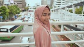 Una muchacha musulmán sonriente está caminando en la transición sobre tráfico por carretera indonesia almacen de video