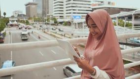 Una muchacha musulmán sonriente joven se coloca en un puente en el centro de la ciudad sobre el tráfico por carretera con una tab almacen de video
