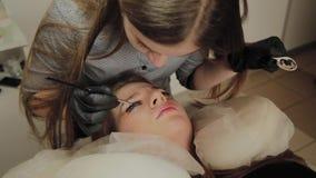 Una muchacha muy hermosa en un salón de belleza hace una laminación azota El cosmetólogo pone la pintura en las pestañas almacen de video