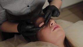 Una muchacha muy hermosa en un salón de belleza hace una laminación azota El cosmetólogo realiza la pestaña del procedimiento almacen de metraje de vídeo