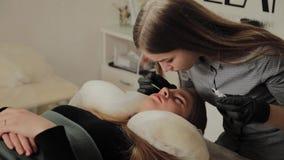 Una muchacha muy hermosa en un salón de belleza hace una laminación azota El cosmetólogo realiza la pestaña del procedimiento almacen de video