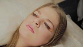 Una muchacha muy hermosa en un salón de belleza hace una laminación azota Para pegamento que espera en las pestañas a secarse almacen de metraje de vídeo