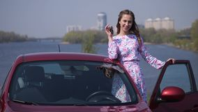 Una muchacha muy hermosa se está colocando en el coche con la puerta abierta, sonrisa, celebrando las llaves en sus manos 4K MES  almacen de metraje de vídeo