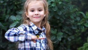 Una muchacha muy linda sostiene una mariposa en su mano, vueltas para enmarcar y sonrisas 4K MES lento almacen de video