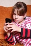 Una muchacha muy seria que juega a juegos en el teléfono Foto de archivo