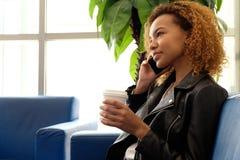 Una muchacha negra hermosa en una chaqueta de cuero con un vidrio de café que habla en el teléfono, sentándose en un sofá azul ce Imagenes de archivo