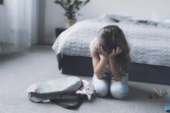 Una muchacha negro-cabelluda se sienta en el piso al lado de su mochila gris y llora encima su cara con sus manos Fotografía de archivo