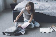 Una muchacha negro-cabelluda se sienta en el piso y la recoge ropa en una mochila gris para escaparse de hogar Imagenes de archivo