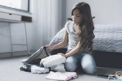 Una muchacha negro-cabelluda triste se sienta en el piso cerca de la cama y recoge cosas en una mochila gris Foto de archivo libre de regalías