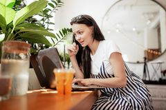 Una muchacha oscuro-cabelluda sonriente hermosa, vestida en estilo sport, trabaja difícilmente en una cafetería moderna Facial en imagen de archivo