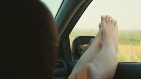 Una muchacha pegándose hacia fuera las piernas en un coche de la ventana abierta La mujer joven le gusta viajar en coche, concept almacen de video
