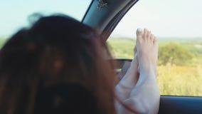 Una muchacha pegándose hacia fuera las piernas en un coche de la ventana abierta La mujer joven le gusta viajar en coche, concept metrajes
