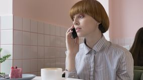 Una muchacha pelirroja hermosa joven se está sentando en un café, usando un smartphone, contestando a una llamada de teléfono, ha almacen de metraje de vídeo