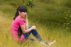 Una muchacha pensativa con las malas hierbas Imagen de archivo libre de regalías