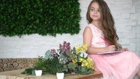 Una muchacha pensativa que el artista se sienta en una tabla entre las flores, que mira alrededor y que dibuja almacen de video