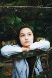 Una muchacha pensativa se coloca en el fondo de hojas verdes Foto vertical fotografía de archivo
