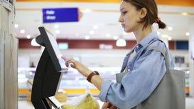 Una muchacha pesa plátanos en las escalas electrónicas en un supermercado y pone una etiqueta engomada con un precio Plátanos en  almacen de video