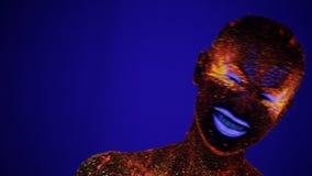 Una muchacha pintada con el polvo fluorescente en la luz ultravioleta ríe metrajes