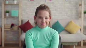 Una muchacha positiva y feliz con un defecto de la persona que mira la sonrisa de la cámara almacen de video