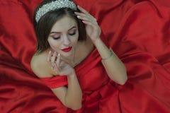 Una muchacha preciosa en un vestido rojo se está sentando en el piso y está llevando a cabo sus manos cerca de su cara Visión des fotos de archivo libres de regalías