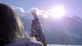 Una muchacha preciosa mira el sol a través de su mano Palma de los juegos en el sol en invierno De vacaciones, ella goza de nieve almacen de metraje de vídeo