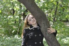 Una muchacha que abraza un árbol Imagen de archivo libre de regalías