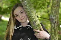 Una muchacha que abraza un árbol Foto de archivo libre de regalías