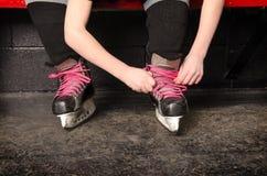 Una muchacha que ata patines del hockey sobre hielo en vestuario Imagen de archivo