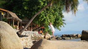 Una muchacha que balancea en un oscilación de la cuerda en la playa
