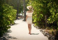 Una muchacha que camina a lo largo de una trayectoria entre las palmeras Alineada blanca tropics maldives Imagen de archivo libre de regalías