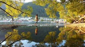 Una muchacha que camina a través de un pequeño río durante otoño en Queenstown, Nueva Zelanda foto de archivo
