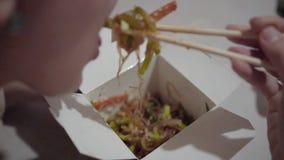 Una muchacha que come los tallarines del wok fuera de la caja usando los palillos en la cocina almacen de video